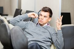 Angry Customer Service Representative Gesturing. While using headset in office Royalty Free Stock Image