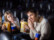 Angry Daughter Looking To Father Using Mobilephone. Angry daughter giving shh expression to father using mobilephone in movie theater Royalty Free Stock Images