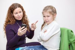 Angry daughter sitting after mother taking her cellphone Stock Photos