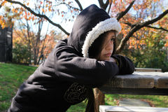 Angry and depressed girl sit in a park. Angry and depressed preteen girl sit in a park royalty free stock images