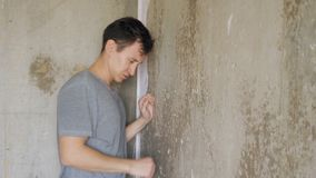 Angry depressed man standing near wall and knocking fists.  stock footage