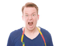 Angry diet. Young man with a measuring tape around his neck livid with his diet - isolated on white Stock Photo