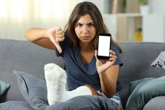 Angry disabled girl showing a blank phone screen Royalty Free Stock Photo