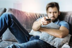 Angry disappointed man looking straight and holding the console. Leave me alone. Angry disappointed unshaken man looking lying on the sofa straight and holding Royalty Free Stock Photos