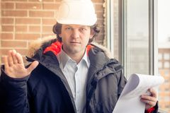 An angry disgruntled builder worker in a helmet with project drawings plans in his one hand and mobile phone in another. Hand screams on someone. Bad executed Royalty Free Stock Images