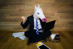Angry and dissatisfied unicorn in a suit and tie shows fist and works at home office. Young man in funny horse mask sits on the floor and works with laptop stock photography