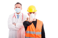 Angry doctor and constructor showing obscene gesture Stock Photos