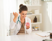 Angry doctor woman making injection into donut Royalty Free Stock Photos