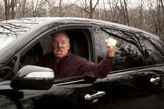 Angry Driver. Waving fist from open window of a black suv Stock Image