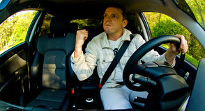 Angry driver. A fisheye view of an angry man driving a car with his fist raised as he is overcome with road rage.  Grain and noise visible in shadow areas of Royalty Free Stock Photos