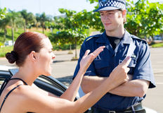 Angry driver. Angry female driver angry at a traffic police over a ticket stock photography
