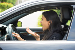 Angry driver. Closeup portrait, angry young sitting woman pissed off by drivers in front of her and gesturing with hands, isolated city street background. Road Stock Images