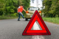 Angry driver kicking the tires on broken car. And red warning trangle Royalty Free Stock Photos