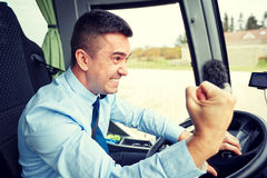 Angry driver showing fist and driving bus Royalty Free Stock Images