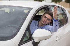 Angry driver stuck at traffic jam watching outside car. Window Stock Photos