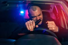 Angry drunk man sitting in car with beer bottle. Auto chased by police Stock Photography