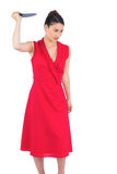 Angry elegant brunette in red dress holding knife Royalty Free Stock Photos