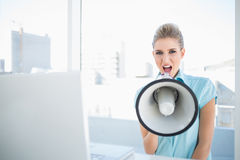 Angry elegant woman shouting in megaphone. In bright office Stock Images