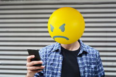 Angry emoji head man. Using a smartphone stock photos