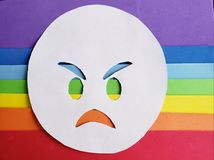 Angry emoticon on white and background with rainbow colors. Lgbt community, multicolor lines and stripes, expression and diversity royalty free stock photo