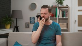 Angry, emotional bearded man screaming at smartphone. Stressed and depressed guy calling to girlfriend and start. Screaming in the living room. Indoor stock footage