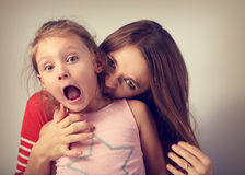 Angry emotional young mother wanting to bite her naughty caprici. Ous daughter with screaming nervous frightened face and open mouth. Humor concept portrait Royalty Free Stock Photo