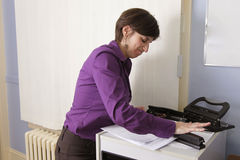 Angry employee with stapler. A young woman takes her frustration out on office equipment stock photos