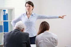 Angry employer. Young angry employer throwing two employees out of the door stock image
