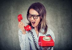 Angry enraged business woman yelling at the red telephone stock photography