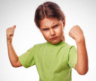 Angry evil girl shows fists experiencing anger and. Anger emotions isolated gray Royalty Free Stock Image