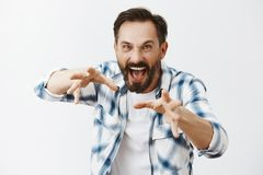 Angry evil magician in casual shirt pulling hands towards camera in fron of chest and casting magic spell to kill enemy. Wanting choke someone with mad and royalty free stock photography