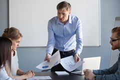 Angry executive architect scolding stressed incompetent employee. Angry mad male boss executive architect or designer shouting reprimanding scolding stressed stock photo
