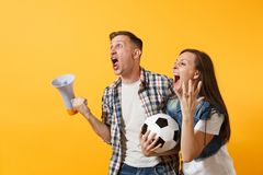 Angry expessive crazy couple, woman man football fans screaming, upset of loss, goal of favorite team with soccer ball royalty free stock photos