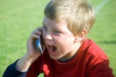 Angry Expression/Cell Phone. Young boy making a silly expression while talking on cell phone. Maybe he's yelling to be heard, or in training to be a CEO one day Royalty Free Stock Images