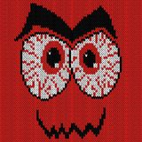 Knitted grimace with angry bloodshot eyes. Angry expression grimace with bloodshot eyes, knitting vector pattern as a fabric texture Stock Image