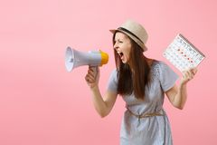 Angry expression wild woman screaming in megaphone, holding periods calendar for checking menstruation days isolated on. Pink background. Medical healthcare stock image
