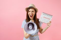 Angry expression wild woman screaming in megaphone, holding periods calendar for checking menstruation days isolated on. Pink background. Medical healthcare stock photo