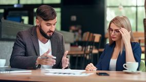 Angry fashion male boss and employee woman talking working at team meeting pointing on document. Angry fashion male boss and focused employee woman talking stock video footage