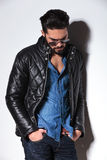 Angry fashion man in leather jacket and sunlasses posing. Against studio wall Royalty Free Stock Photography