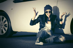 Angry fashion punk woman sitting next to her car Royalty Free Stock Image