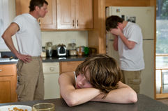 Angry father. Father faces off with older son; younger son is miserable stock images