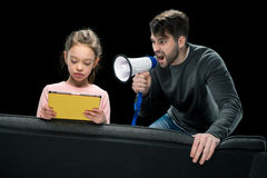 Angry father with megaphone screaming at upset daughter using digital tablet Royalty Free Stock Photography