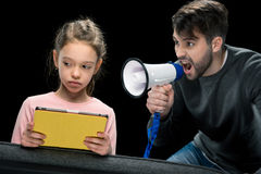 Angry father with megaphone screaming at upset daughter using digital tablet Stock Photography