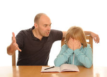 Father angry with daughter. Angry father sitting at desk beside daughter upset after  trying unsuccessfully to do her homework on white background Stock Photo