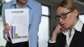 Angry female boss shouting at guilty worker holding deadline document, stress stock video footage
