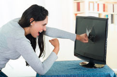 Angry female brunette punching computer screen Royalty Free Stock Photo