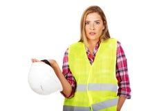Angry female builder holding helmet Stock Images