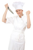 Angry female cook with knife and raised fist Stock Photos