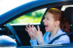 Angry female driver. Closeup portrait displeased angry pissed off aggressive woman driving car, shouting at someone, hands up in air isolated traffic background Stock Image