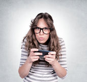 Angry female. Holding the mobil phone. Selective focus on the female Royalty Free Stock Image